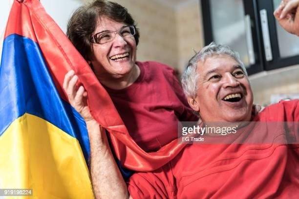fan colombiano pareja senior viendo partido de fútbol en casa - bandera colombiana fotografías e imágenes de stock