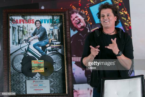 Colombian singer Carlos Vives gestures during a press conference after reaching the gold and triple platinum disc with his album 'La Bicicleta' at...