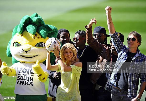 Colombian singer Shakira flanked by Zakumi the official tournament mascot and local artists holds the Jo'bulani football that will be used for the...