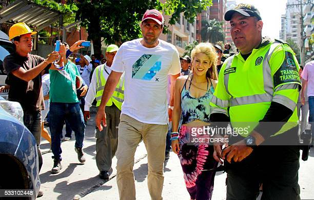 Colombian singer Shakira is scorted by a policeman during the recording of the video for the song La Bicicleta in which she performs with Colombian...