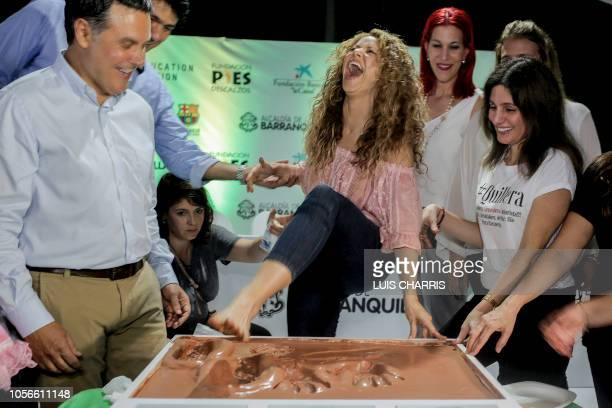Colombian singer Shakira places her foot on a cement cornerstone on November 2 in Barranquilla Colombia during the groundbreaking ceremony for the...