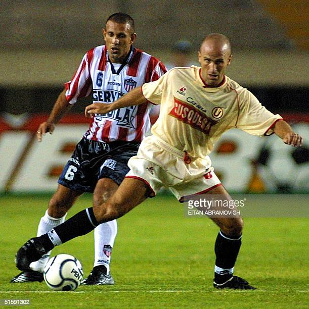 Colombian soccer player Juan Ramirez of the Junior fights for the ball with Peruvian Gustavo Grondona of the Lima Universtity team 15 March 2001...