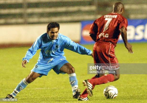 Colombian soccer player Tresor Moreno of America de Cali keeps the ball from bolivian Pedro Guiberguis of Bolivar 20 February 2002 in La Paz during...