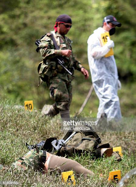 A Colombian soldier and a member of the Colombian Judiciary Police walk past the body of a member of the rigthwing paramilitary gang known as Aguilas...