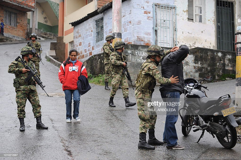 A Colombian soldier frisks a man next to other soldiers in Medellin, Antioquia department, Colombia on May 27, 2010. Colombia will hold presidential elections next May 30. AFP PHOTO/ Raul ARBOLEDA