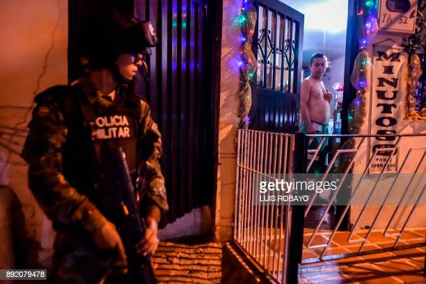 A Colombian soldier looks a man during a patrol in the Siloe neighborhood in Cali Colombia on December 13 2017 By order of Cali´s Mayor Maurice...