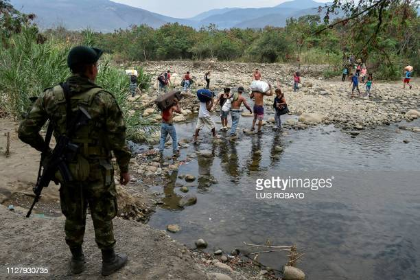 A Colombian soldier looks at people crossing through an illegal trail across the Tachira river from San Antonio Venezuela to Cucuta Colombia on...