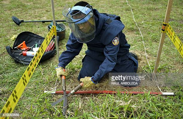 A Colombian soldier practices with a fake mine as part of his training before searching for real land mines as part of the humanitarian demining in...