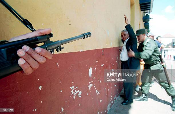 Colombian soldier searches a man for a firearm March 10 2002 in Bogota Colombia The man being frisked is assisting voters in the election for...