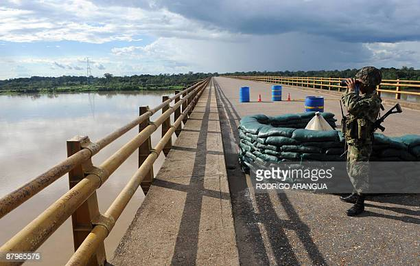 Colombian soldier uses his binoculars as he keeps watch on a bridge over the Guaviare river on the outskirts of the San Jose del Guaviare, in...