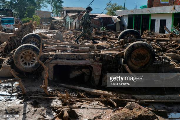 A Colombian soldier walks amid rubble caused by mudslides due to heavy rains in Mocoa Putumayo department southern Colombia on April 4 2017 Colombian...