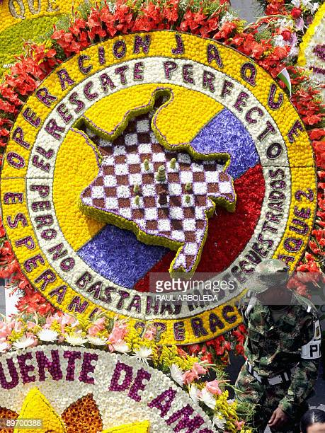 A Colombian soldier walks past a traditional 'silleta' in the shape of the map of Colombia and referring to 'Operation Check' during the Flower...