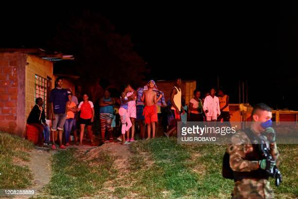 Colombian soldier wearing a face mask as a preventive measure against the spread of the COVID-19 coronavirus stands guard in front of residents in...