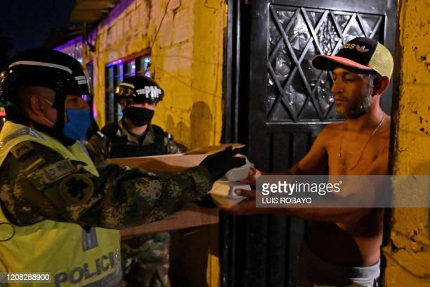Colombian soldier wearing a face mask delivers food to low-income residents, as a measure of help to prevent the spread of the COVID-19 coronavirus...