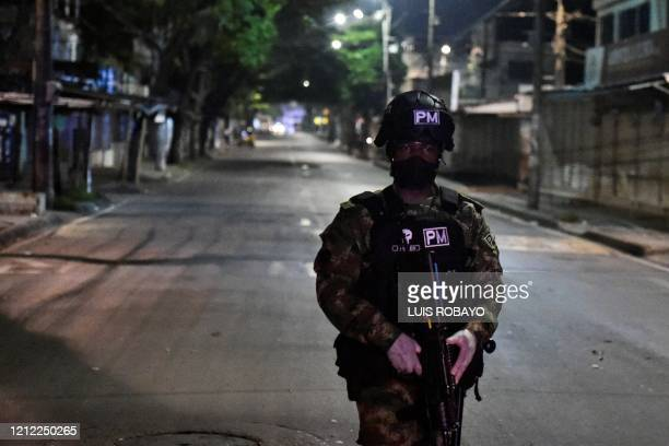 Colombian soldier wearing a face mask walks on a street during the start of a curfew in Cali, Colombia on May 8, 2020. - Authorities from the city of...