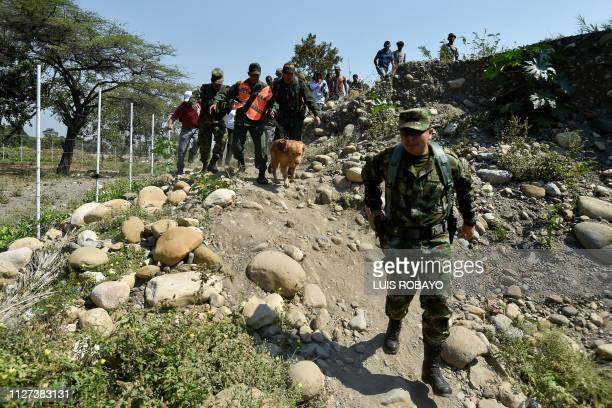 Colombian soldiers escort a member of the Bolivarian National Armed Forces of Venezuela who deserted to Colombia with his dog in Cututa on February...