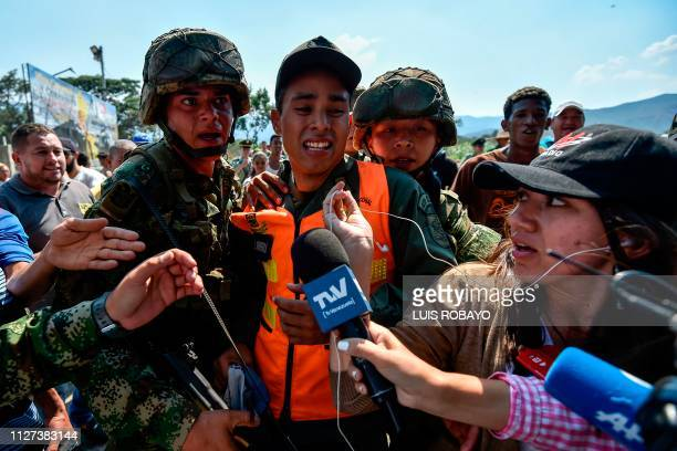 TOPSHOT Colombian soldiers escort a member of the Bolivarian National Armed Forces of Venezuela who deserted to Colombia with his dog in Cututa on...