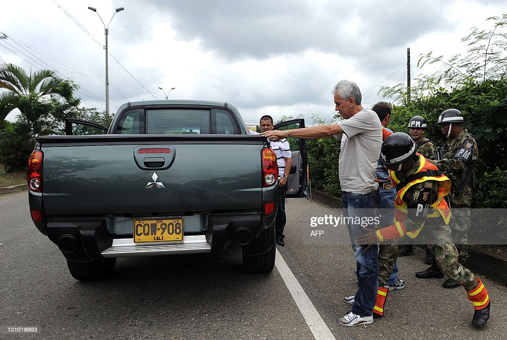 Colombian soldiers frisk a car driver at a checkpoint in Cali, Valle del Cauca departament, Colombia, on May 27, 2010. Colombia will hold presidential elections next May 30. AFP PHOTO/ Luis ROBAYO