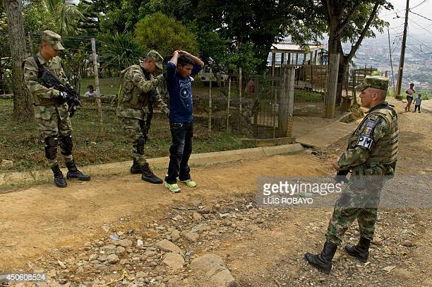 Colombian soldiers frisk a man in a street of Cali Colombia on June 14 during security operations on the eve of the presidential runoff which will...