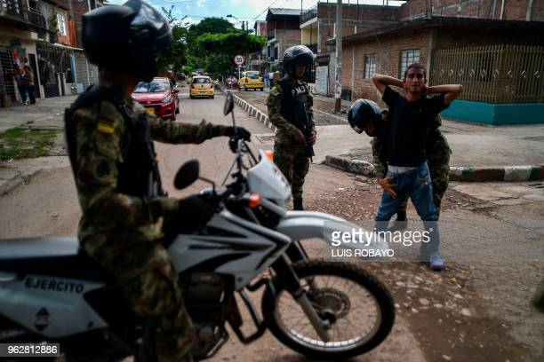 Colombian soldiers frisk a young man at a checkpoint in Cali Colombia during a security operation on the eve of presidential elections on May 26 2018...