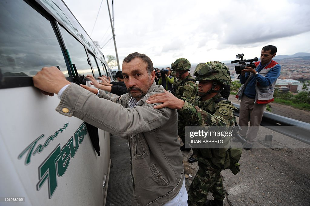 Colombian soldiers frisk passengers of a small bus at a checkpoint in Bogota, on May 28, 2010. Colombia will hold presidential elections next May 30.
