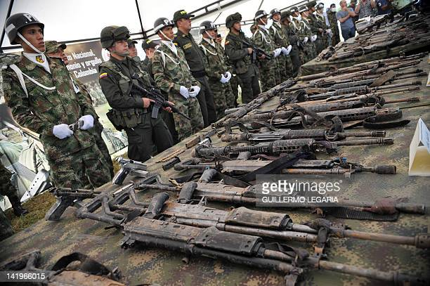 Colombian soldiers guard next to the guns seized on the eve during a joint operation of the army air force and police against FARC guerrillas in the...