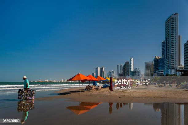 Colombian street vendor walks along umbrellas on the beach in Bocagrande a wealthy neighborhood on December 17 2017 in Cartagena Colombia After the...