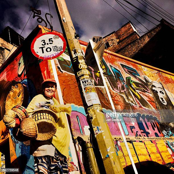 Colombian street vendor walks around a street corner covered in colorful graffiti artwork and posters in La Candelaria Bogota Colombia 19 February...