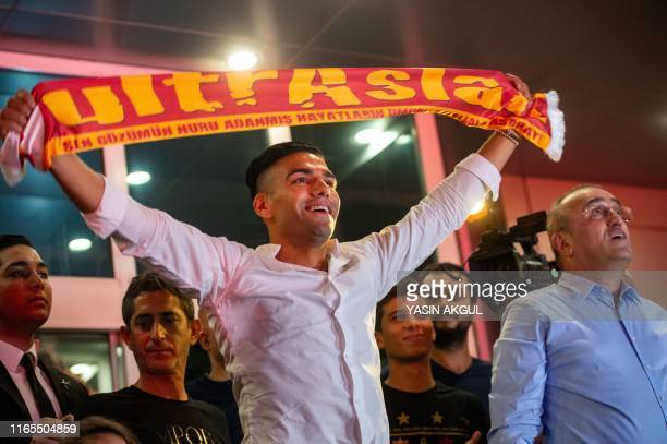 Colombian striker Radamel Falcao holds up a Galatasaray fan scarf as he arrives at Ataturk Airport in Istanbul on September 1 after French L1 AS...