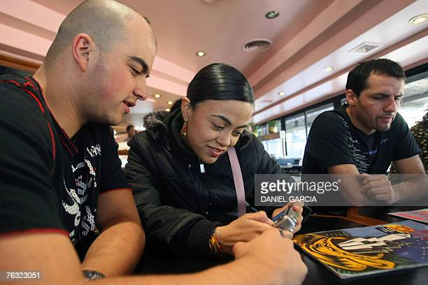 Colombian tango dancer Gina Medina looks at a digital camera's screen with her boy friend Andres Jaramillo while her partner Ivan Ovalle checks the...