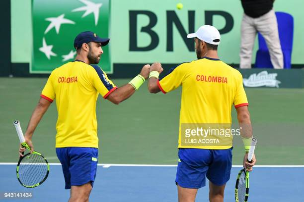 Colombian tennis player Juan Sebastian Cabal celebrates with his teammate Robert Farah after winning a point against Brazilian tennis players Marcelo...
