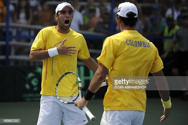 Colombian tennis player Juan Sebastian Cabal celebrates with partner Robert Farah after winning a point against Uruguay during their Davis Cup...