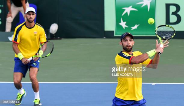 Colombian tennis player Juan Sebastian Cabal returns a ball as teammate Robert Farah looks against Brazilian tennis players Marcelo Melo and Marcelo...