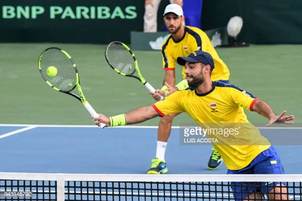 Colombian tennis player Juan Sebastian Cabal returns a ball as teammate Robert Farah looks against Brazilian tennis players Marcelo Melo and Marcelo...