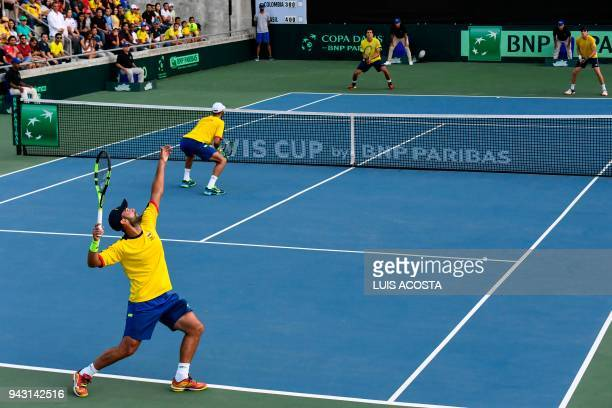 Colombian tennis player Juan Sebastian Cabal serves next to his teammate Robert Farah against Brazilian tennis players Marcelo Melo and Marcelo...