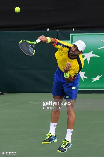 Colombian tennis player Robert Farah returns a ball against Brazilian tennis players Marcelo Demoliner and Marcelo Melo during their Americas Zone...