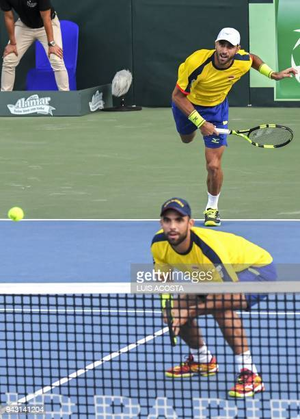 Colombian tennis player Robert Farah returns a ball as teammate of Juan Sebastian Cabal bends during their Americas Zone Group I 2nd round Davis Cup...