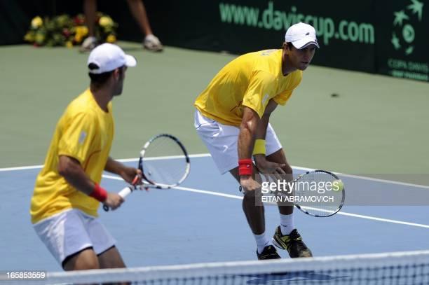 Colombian tennis player Robert Farah returns the ball as partner Juan Sebastian Cabal looks on during their Davis Cup Americas Group I second round...
