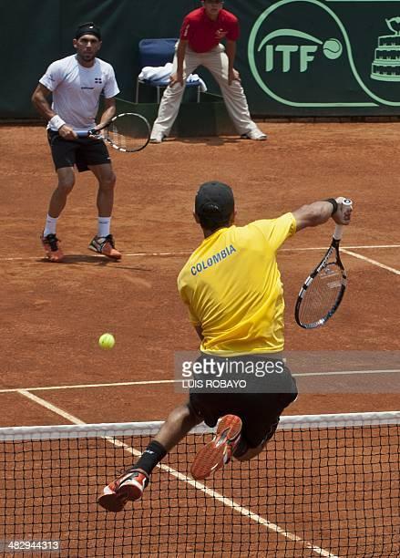 Colombian tennis player Robert Farah returns the ball to Dominican Republic's tennis players Jose Hernandez and Victor Estrella during their Davis...