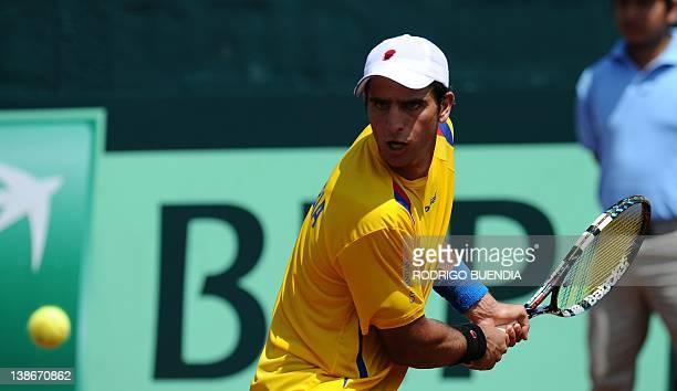 Colombian tennis player Robert Farah returns the ball to Ecuador's Julio Camposano during their Davis Cup match in Salinas Ecuador on February 10...