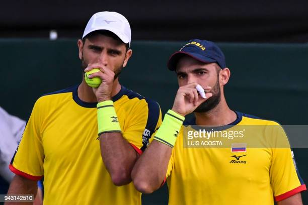 Colombian tennis player Robert Farah speaks with his teammate Juan Sebastian Cabal during their Americas Zone Group I 2nd round Davis Cup tennis...