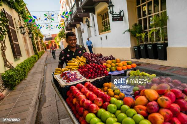Colombian vendor pushes a cart loaded with fruits for sale on the street of Getsemaní a popular artistic neighborhood on December 16 2017 in...