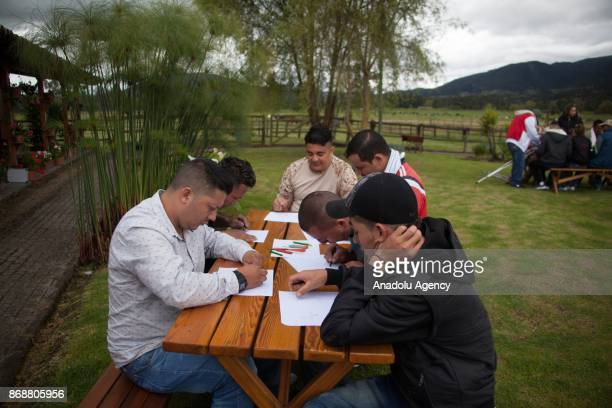 Colombian war victims are seen as they make a drawing during a therapy inside a horse therapy rehabilitation area for the Colombian soldiers victims...