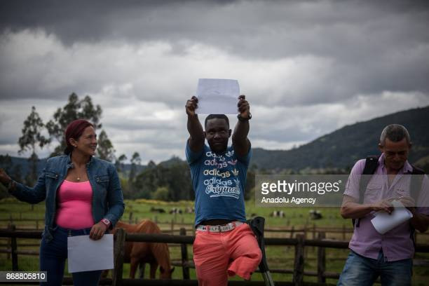 Colombian war victims show their drawing during a therapy inside a horse therapy rehabilitation area for the Colombian soldiers victims of landmines...