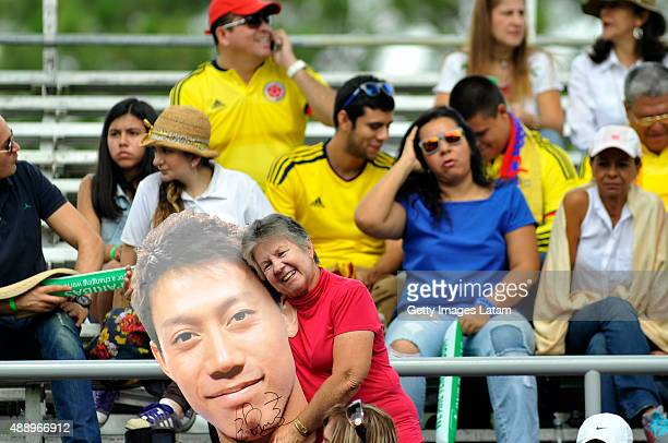 Colombian woman poses for a picture with a photograph of Kei Nishikori of Japan during the Davis Cup World Group Playoff singles match between...