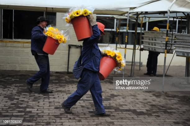 Colombian workers carry buckets wiht flowers at Flores de Funza farm in Funza Cundinamarca department Colombia on January 28 2010 Since late 2009...