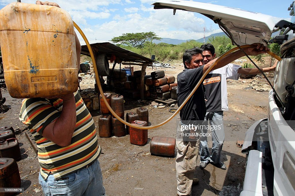 Colombians fill up jerry cans with gasoline smuggled in a truck in Cucuta, Colombia, in the border with Venezuela on August 24, 2009. In Venezuela the price of oil is 50 times cheaper than in Colombia, and due to the crisis between both countries, Colombians started smuggling along the border. Venezuela will not renew a recently-expired deal that provided Colombia gasoline at cut-rate prices. This situation expanded with cross-border tensions over Colombia's decision to allow US troops and contractors to use seven of its military bases for anti-drug and anti-terrorism operations.