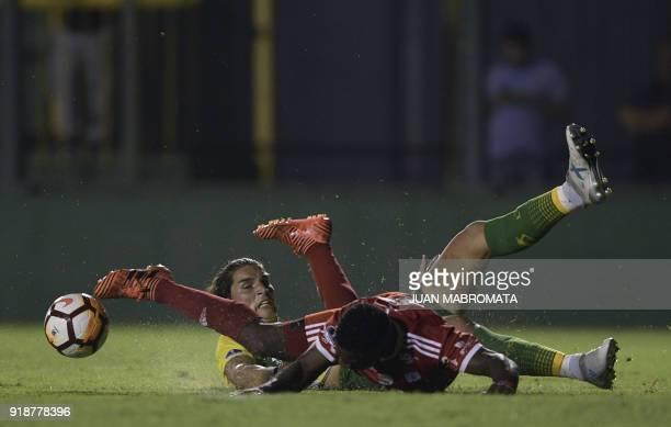 TOPSHOT Colombia's America de Cali forward Cristian Arboleda is fouled by Argentina's Defensa y Justicia Swiss defender Dylan Gissi during their Copa...