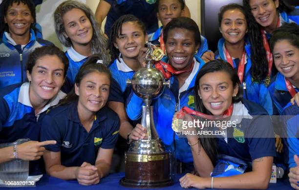 Colombia's Atletico Huila players pose with the Copa Libertadores Women trophy during a press conference in Bogota Colombia on December 4 2018...
