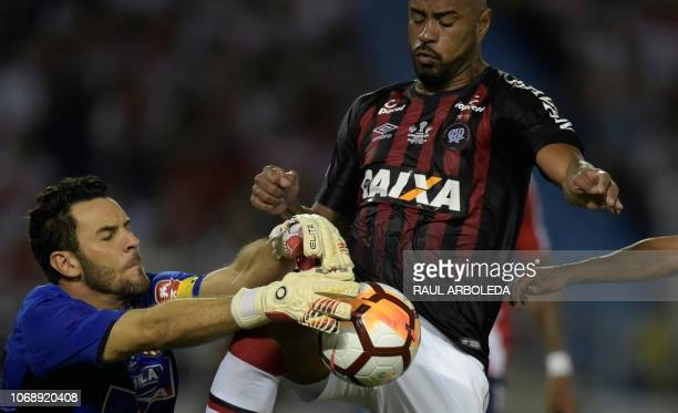 Colombia's Atletico Junior goalkeeper Sebastian Viera vies for the ball with Brazil's Atletico Paranaense Thiago Heleno during their Copa...